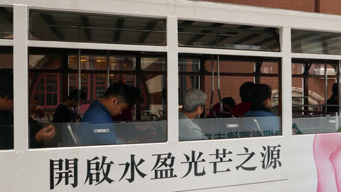 Chinese commuters in double-decker tram, panning shot of second floor, close Footage