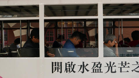 Chinese commuters in double-decker tram, panning shot of... Stock Video Footage