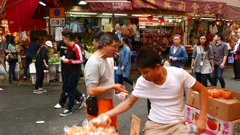 Young men put oranges to tray, outdoor market corner, parallax shot Footage