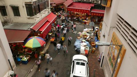 People fuss around street, market stalls around building... Stock Video Footage