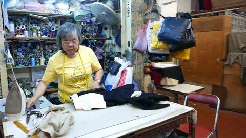 Chinese lady work at sewer stall, tiny atelier workshop Stock Video Footage