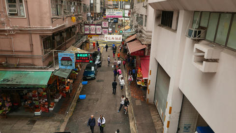 Citizens walk along Wan Chai road at Bowrington Market area, slide shot above Footage
