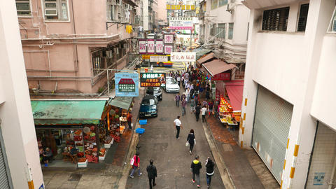 White car slowly drive through Wan Chai road, people walk around Footage
