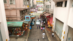White car slowly drive through Wan Chai road, people walk... Stock Video Footage