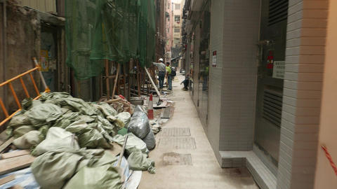Construction works at narrow passage, tall building... Stock Video Footage