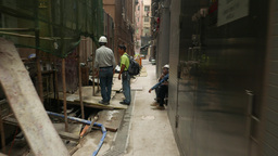 Construction works at narrow passage, tall building backside, worker stand Footage