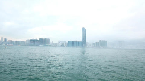 Cloudy harbour shore from opposite side, evening haze, white vessel on water Footage