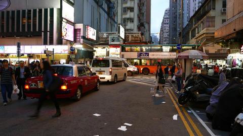 Pedestrian walk crossing dark street, taxi car drive beside, bright shops ahead Footage