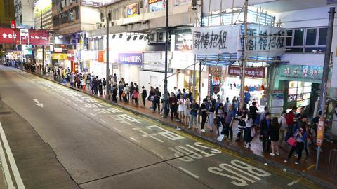 Empty night city street, people crowd along sidewalk wait... Stock Video Footage