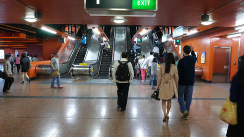 Escalators at Tin Hau MTR station, commuters walk to and from, concourse hall Footage