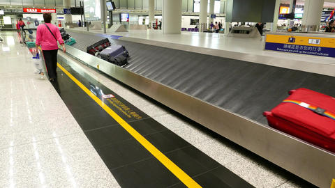 Passenger walk along luggage claim conveyor, suitcases move towards Footage