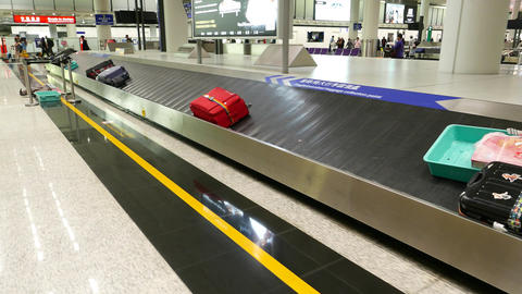 Big red suitcase move on conveyor, baggage carousel, track shot Footage