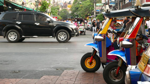 Tuk-Tuk driver waiting for customers, auto rickshaw stand against lively street Footage