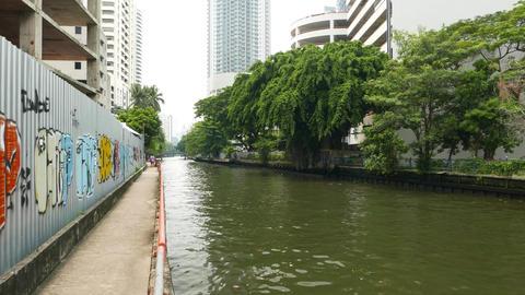 POV camera move backwards along concrete walkway, city canal block backyard area Footage