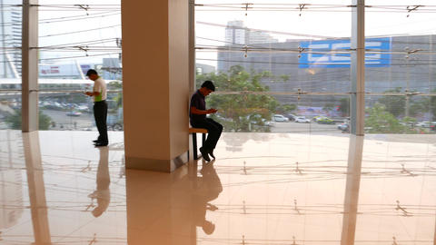 Empty Hall In Business Building Man Sitting Near Wall Window, Look To Smartphone stock footage