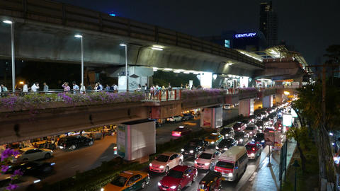Commuters walk along elevated passage above driveway, track shot, night time Footage