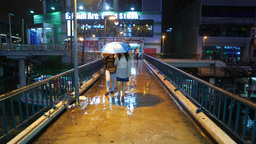 Strong rainfall at dark evening, woman with umbrella come towards on footbridge Live Action