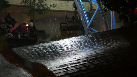 Rainfall drops shimmer in light beam, wet roof close view, night urban scene Footage