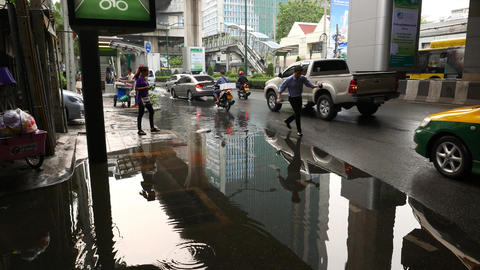 Man crossing puddle on pavement, slowly step from stone…, Live Action