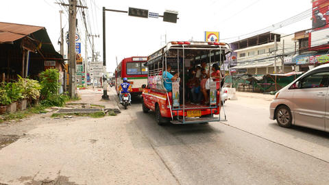 Baht bus with passengers slowly drive along busy road, follow camera Footage