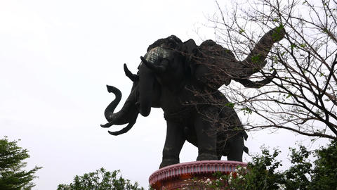 Giant three head elephant sculpture in dusk, low angle slide shot Footage