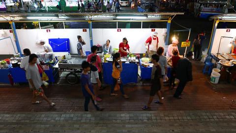 Street food stalls at passage, night time, side view, Asian people Footage