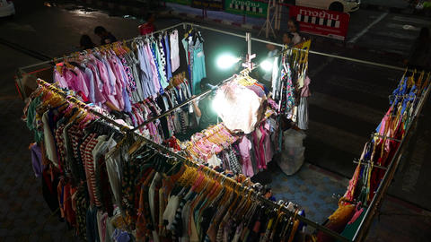 Rack with women garments and clothing hanging on, night street market Footage