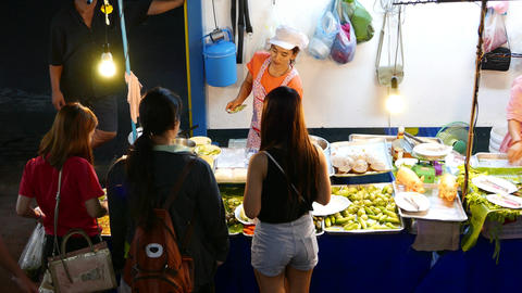 Young Thai woman serve clients night stall of traditional meal, packed to home Footage