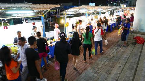 Local Thai People Walk Aside Stalls, Night Street Food Market Against Mall stock footage
