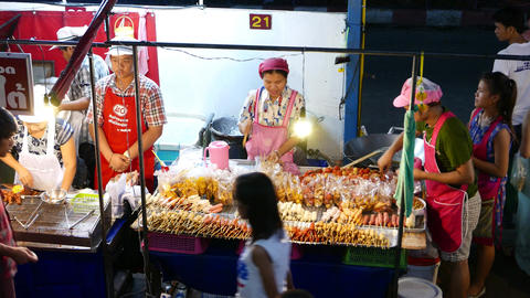 Stall full of cooked and raw satay, dried foods, snacks in plastic, night street Footage