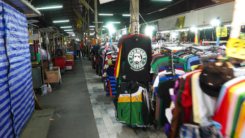 Walk through aisle at empty night street marketplace, garments hanging around Footage