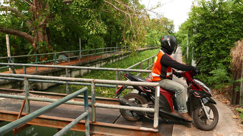 Vacant motorcycle taxi drive through steel gangway, narrow bridge at rural place Footage