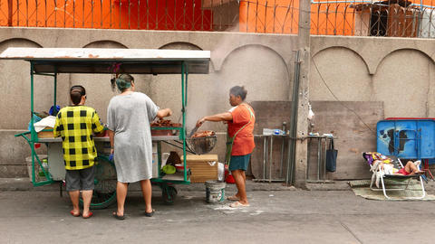 Thai women cooking at cart kitchen, her young son sleep aside on chair Footage
