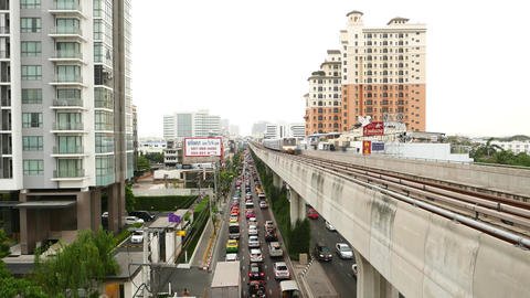 Rapid transit train approaches on elevated railways, above traffic jam Footage