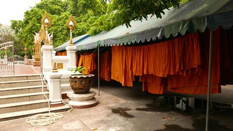 Orange kasaya clothes drying under tent awning, monk monastery backyard Footage