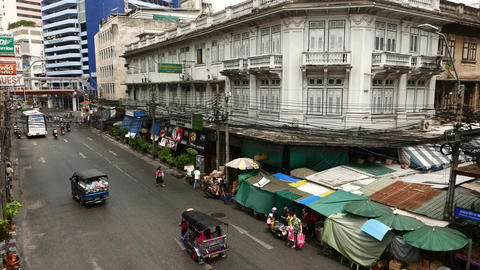 White building with closed windows and balcony, lively inner-city area of BKK Footage