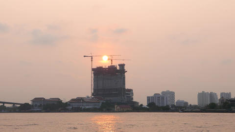 Urban Sunset Over River, Tower Construction Site And Sun Disc, Bangkok Cityscape stock footage