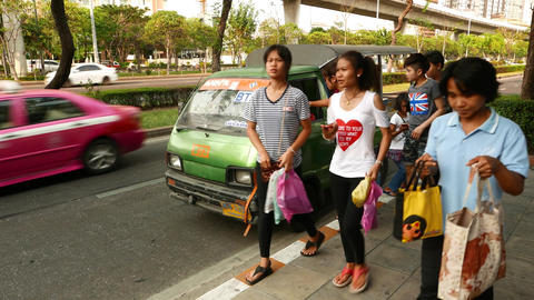 Tiny songthaew commuters alight from, people pay baht to driver the fare Footage