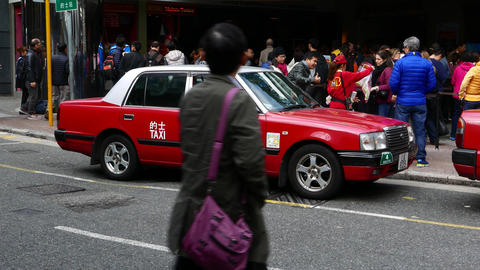 Traditional red toyota crown taxi against people queue, Hong Kong Footage