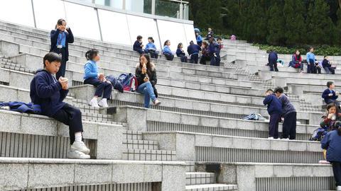 Little schoolboy sit on amphitheater stairs. Lunch break Footage