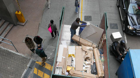 Long shot: man sort and pack building waste in truck Footage