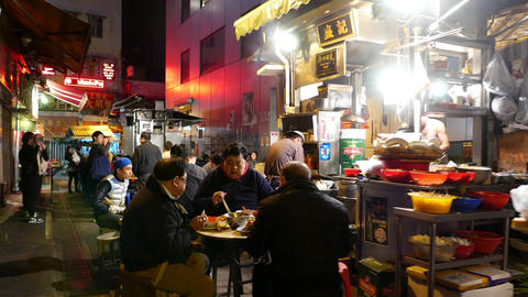 Authentic outdoor eatery on dark urban alley, people seat and eat supper Footage
