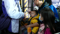 Parent gives baby bottle to the child. Crowded public area Footage