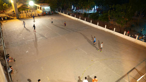 Minifootball game on hard field, night time, outdoor playground Footage