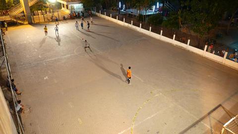 Thai people play mini football on small hard field, night time, top view Footage