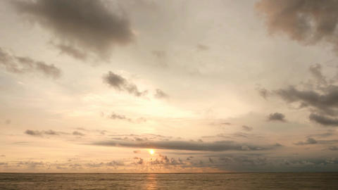 Sunset timelapse, clouds and seascape, sundisc appear behind cloud and move down Footage