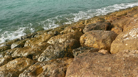 Wave breaker stones closeup, calm emerald-colored sea water splashe about rock Footage