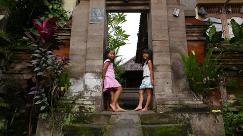 Balinese children standing smiling at stone gate, tilt camera Footage
