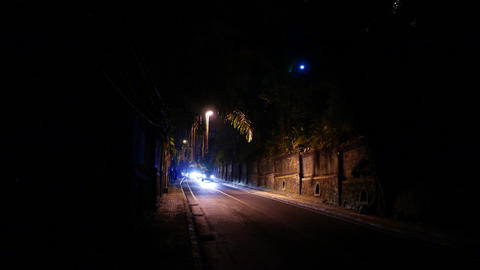 Dark cutting road single lamp in middle, brightly illuminated with car headlight Footage