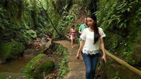 People walk berm bottom of rocky gorge, glide shot, move towards Footage
